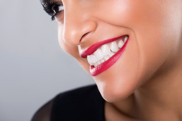 Beautiful laughing woman with red lips and white teeth, closeup