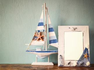 vintage nautical frame with wooden boat on wooden table. retro f