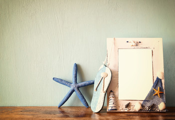 vintage nautical frame with starfish on wooden table. retro filt