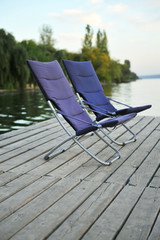 Two blue folding chairs on  wooden platform on the river