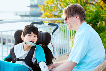 Father talking with his disabled son in wheelchair outdoors