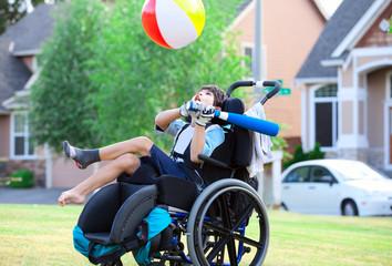 Disabled boy hitting ball with bat at park