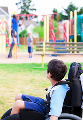 Disabled little boy in wheelchair watching children play on play