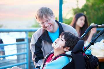 Father talking with disabled son in wheelchair outdoors by lake