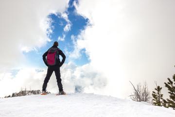 Wall Mural - Uomo osserva cielo con nuvole in montagna d'inverno con ciaspole
