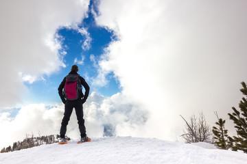 Wall Mural - Persona osserva cielo in montagna d'inverno con ciaspole