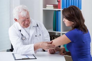 Orthopaedist diagnosing painful elbow