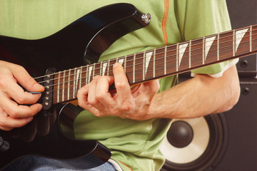 Hands of rock guitarist playing the electric guitar