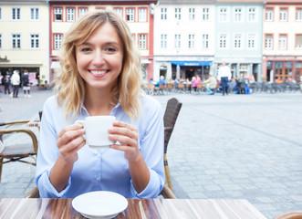Frau mit blonden Locken bei einem Kaffee im Freien