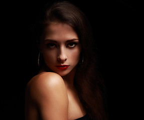 Sexy makeup female in shadows on black background