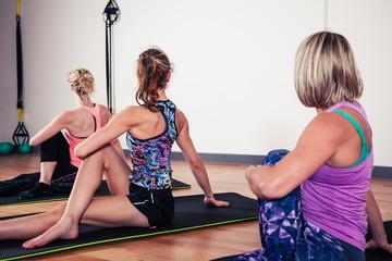 Women stretching their backs in gym