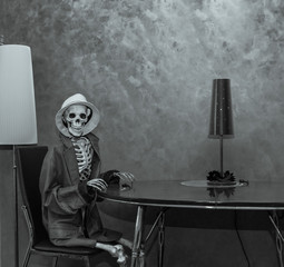 Skeleton sitting behind the table in dark dramatic room