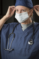 Female Doctor or Nurse Putting on Protective Face Mask