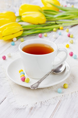 Cup of tea with bonbon with a spring flowers