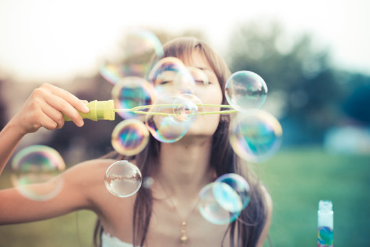 beautiful young woman with white dress blowing bubble