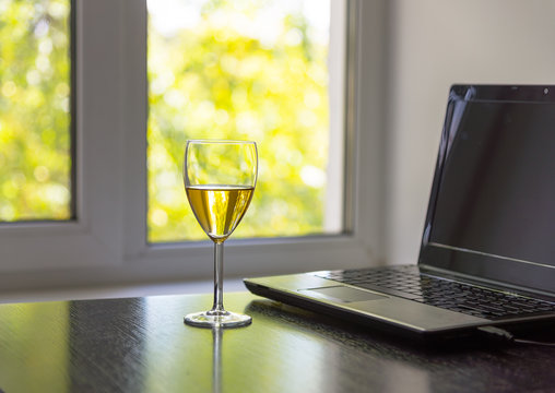Glass of white wine and laptop in front of the window