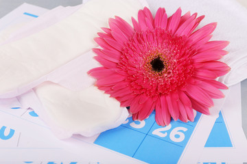 Sanitary pads, and pink Berber and on blue calendar background