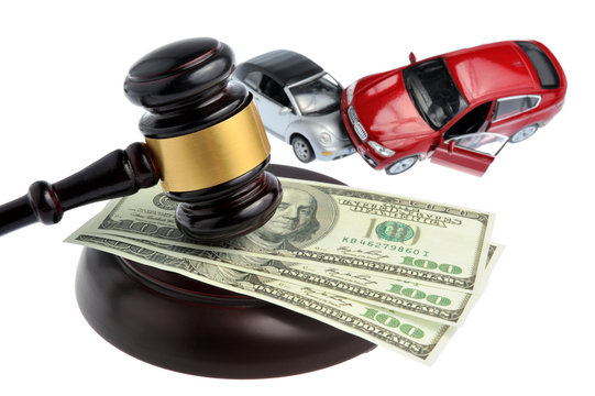 Hammer of judge with money and toy cars isolated on white