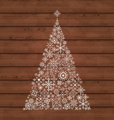 Christmas pine made of snowflakes on wooden background