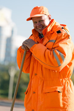Positive caucasian worker with broom tool at city background