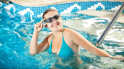woman in bikini and goggles smiling at camera at swimming pool