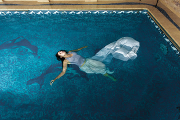 woman in long white dress swimming on water surface at swimming