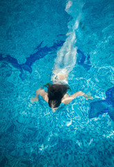 woman covered in long white fabric swimming underwater at pool