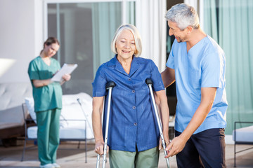 Male Nurse Helping Senior Woman To Use Crutches