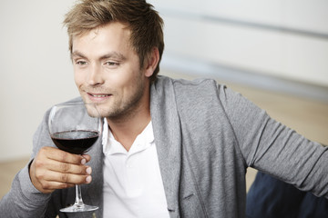Mid adult man relaxing with glass of red wine
