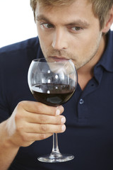 Mid adult man smelling red wine