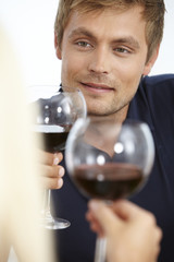 Mid adult couple enjoying glass of red wine