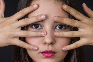 beautiful young asian girl with her fingers on her face