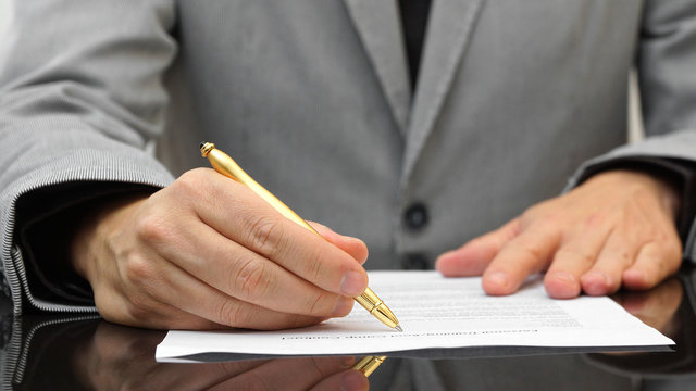 businessman is reviewing agreement with gold pen