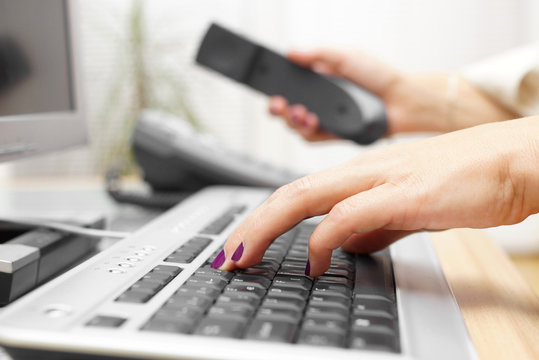 Businesswoman is typing on keyboard and answer the call. custome