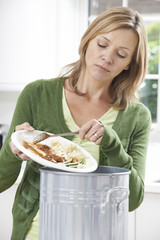 Woman Scraping Food Leftovers Into Garbage Bin