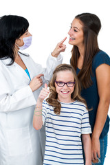Little girl together with older sister ready for dental check up