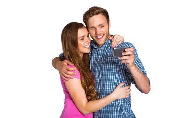 Cheerful young couple taking selfie with smart phone