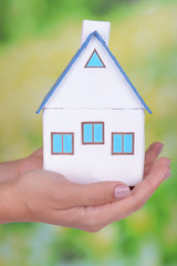 Woman hands holding small house on bright background