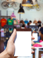 white blank notebook in woman hand and shopping background