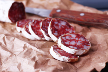 French salami and knife on craft paper background