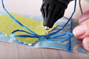 Woman's hand making postcard with a help of glue gun