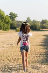Teen girl in a wreath of daisies walketh in  field