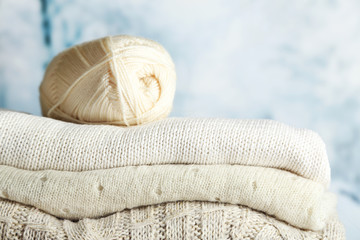 Knitting clothes and yarn on light winter background