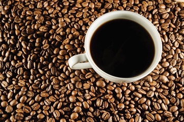 white cup of coffee on coffee beans
