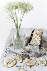 homemade cookies on box on white wooden table with wildflowers