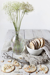homemade cookies on bowl on white wooden table with wildflowers