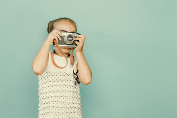 child holding a instant camera
