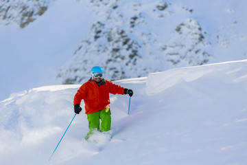 Skiing, Skier, Freeride in fresh powder snow - man skiing downhi