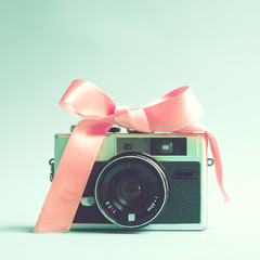 Vintage camera with pink ribbon over turquoise background