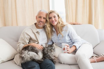 Happy couple with pet cat on sofa